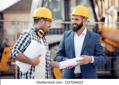 Two engineers with blueprint plan at construction site.