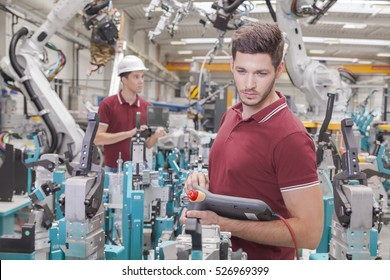 two engineers check functionality while commissioning a production line in welding shop