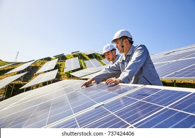 Two engineers are conducting outdoor inspection of solar photovoltaic panels