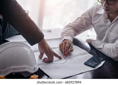 Two engineers are consulting on building design. Teamwork success is a technique of successful work.