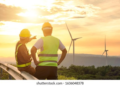 Two engineers discussed the plan for the maintenance of wind turbines. Renewable energy with wind generator by alternative energy concept in Asia