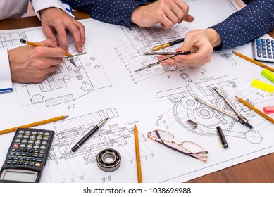 Two engineers discussing an engineering drawing office
