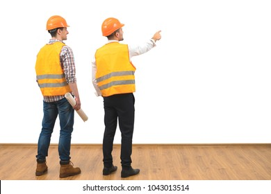 The two engineers gesture on the white wall background