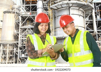 Two engineers going through routine checks, working at a petrochemical oil refinery