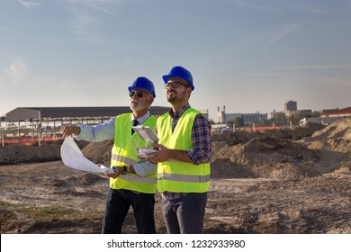 Two engineers with helmets and vests operating with drone by remote control and looking up in the sky. Technology innovations in construction industry
