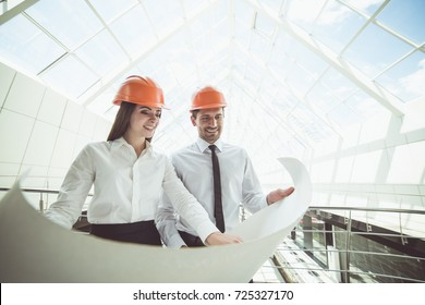 The two engineers hold the project plan in the building