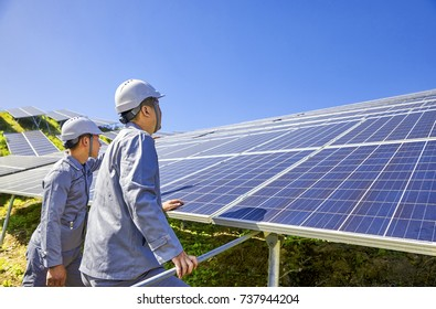 Two engineers are inspecting outdoor solar photovoltaic panels