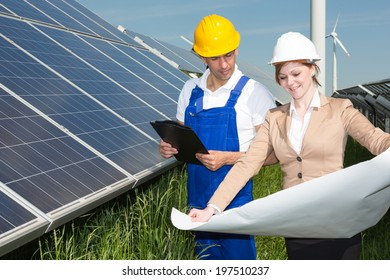 Two engineers looking at construction plan of solar panels