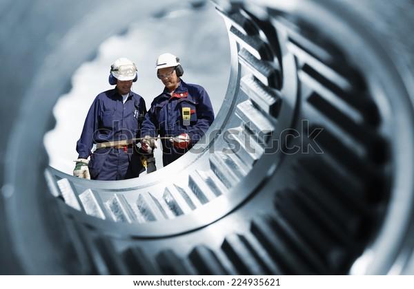 two engineers seen through a large cogwheels gear shaft, metal industry