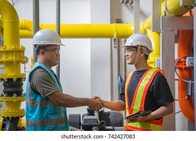 Two engineers shaking hand in the boiler room,maintenance checking technical data of heating system equipment,Thailand people,Discuss the issue about the pipe pressure.