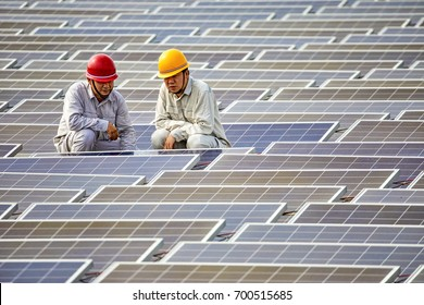 Two engineers squatted on the patrol water floating solar photovoltaic