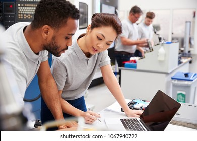 Two Engineers Using CAD Programming Software On Laptop