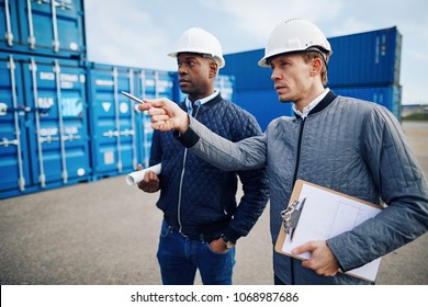 Two engineers wearing hardhats talking together while standing on a large commercial shipping dock tracking inventory
