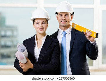 Two engineers in white hard hats keeping level and blueprints. Concept of successful construction