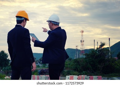 Two engineers are working with tablet on industry background in evening time. Construction manager is planning with engineer guy.