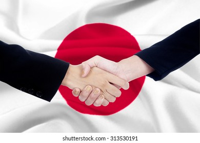 Two entrepreneurs in business suit, shaking hands in front of a japanese flag background