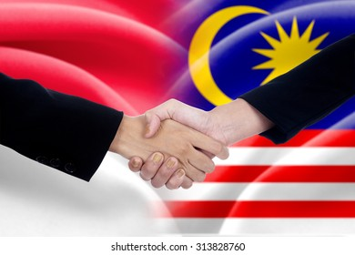 Two entrepreneurs shaking hands after good deal in front of the indonesian and malaysian flags