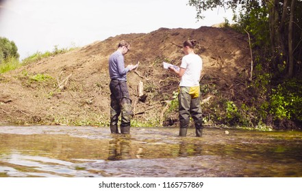 Two environmental scientists standing in the water. A woman checking with the GPS navigator and marking point of research on the map