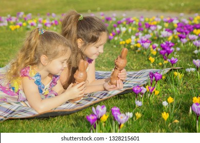 Two equally dressed little sisters lie on a green lawn among the flowers. Kids hold Easter chocolate hares, talk and laugh. Easter holidays, family holidays, joy and spring concept.