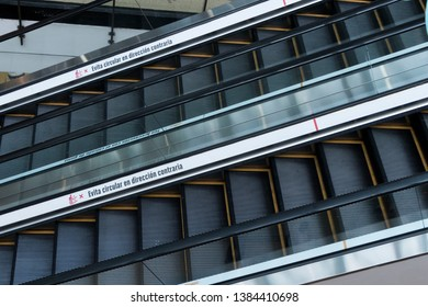 Two escalators in the foreground with a sign in Spanish that says avoid going in the opposite direction