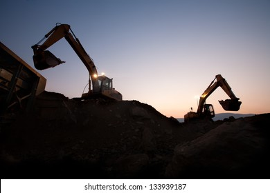 two escavators working on a mine at dawn