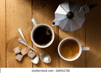 Two espresso and a coffee maker on a rough wooden table (top view)