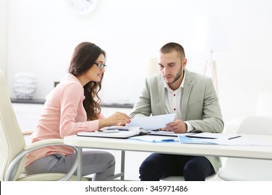 Two estate agents,  in bright office