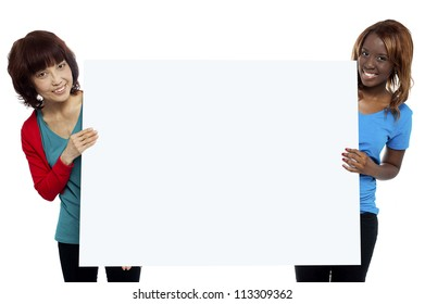 Two ethnic female models presenting whiteboard isolated against white background