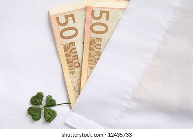 Two euro banknotes and a four-leaf clover in a white shirt pocket