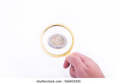 Two euro coin magnified by a magnifying glass on white background