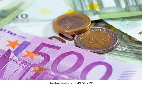 Two Euro coins over bank notes background