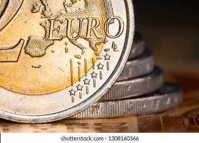 Two euro coins over euro banknotesCoins on a blurred background coin denomination of two euros. Currency of the European Union.