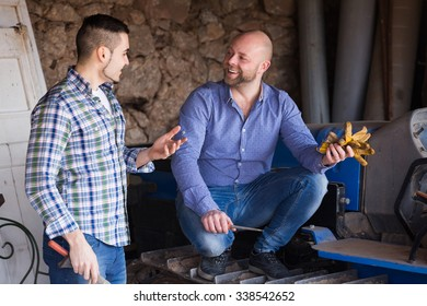Two european mechanics reparing old agrimotors at farm