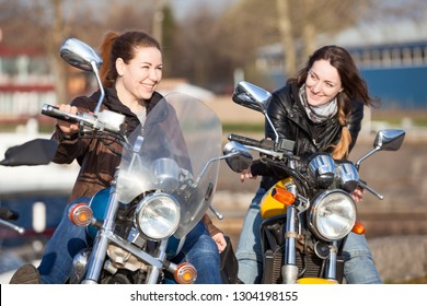 Two European smiling women motorcyclists speaking together while sitting on their motorcycles