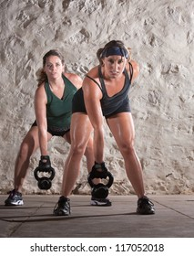 Two European women lifting heavy weights and sweating