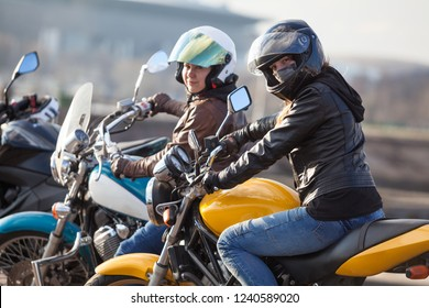 Two European women motorcyclists ready to ride on yellow and blue motorcycles