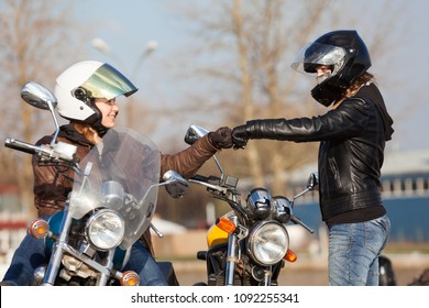 Two European young girls bikers meeting at street with greeting gestures
