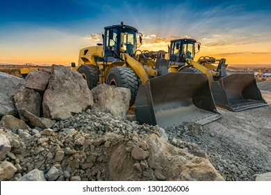 Two excavators moving stone and rock in a construction site