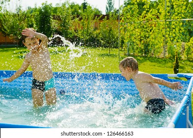 Two excited boys splashing in swimming pool