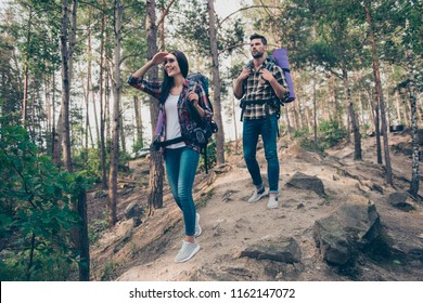 Two excited people with backpacks, spouses couple, wearing casual checkered shirts and jeans, searching way, rout, destination, wandering