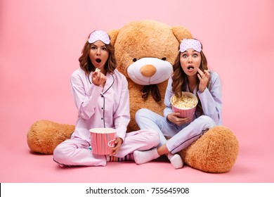 Two excited pretty girls dressed in pajamas sitting with a big teddy bear and eating popcorn isolated over pink background