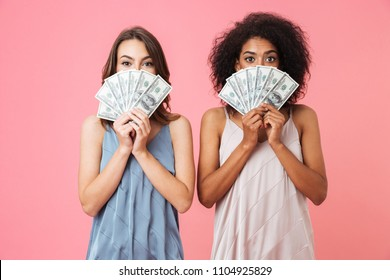Two excited young girls dressed in summer clothes holding money banknotes isolated over pink background