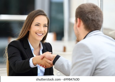 Two executives meeting and handshaking sitting in a coffee shop
