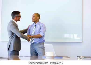 Two executives shaking hands in a meeting room.