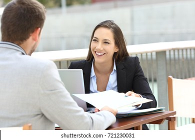 Two executives working sharing informs sitting in a bar terrace