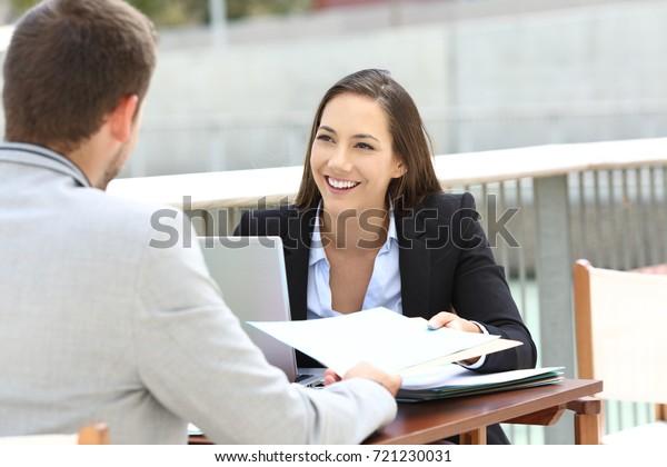 Zwei leitende Mitarbeiter, die Informationen teilen, sitzen auf einer Barterrasse