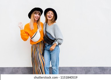 Two  exited hipster women posing over white wall. Fall season. Wearing stylish orange  knitted sweater, black hat , bum bag. Friends spending great time together . Copy space .