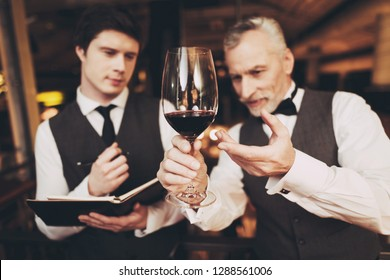 Two experienced sommeliers taste red wine and make wine list in restaurant. Confident sommelier checks aging of wine.