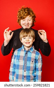 Two expressive brothers studio portrait, red-haired boys isolated on red