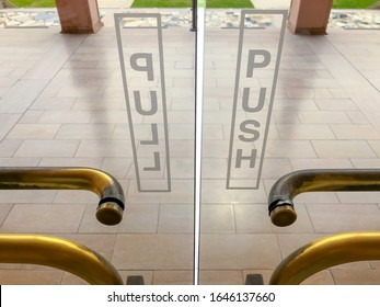 """Two exterior glass doors, one labeled """"Push"""" and the other """"Pull"""", with worn brass handles, at an exit to a tiled patio, for themes of dichotomy, clarification, decisions. Flip photo to reverse."""